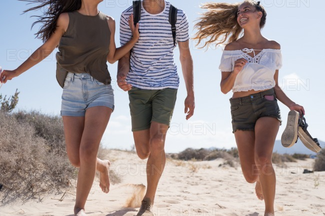Two girls and a boy having fun at the beach stock photo