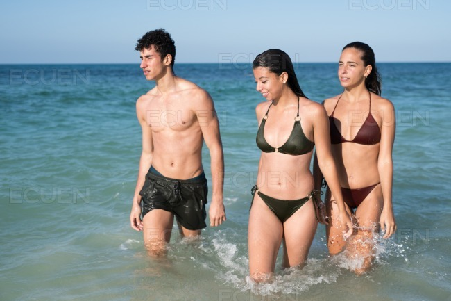 Two girls and a boy in swim wear are wet stock photo