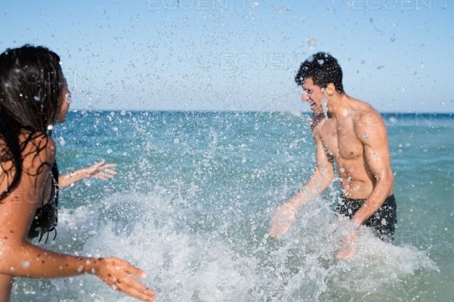 Young couple splashing each other with water stock photo
