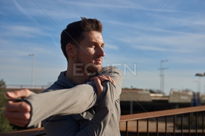 Man hold and stretches his arm in exercise