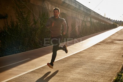 Man in athletic gear sprinting down a road