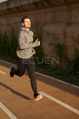Man in fitness gear running on a road