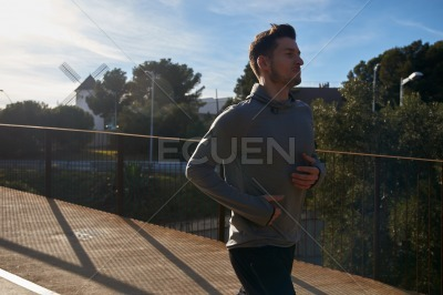 Man running next to a fence on a road