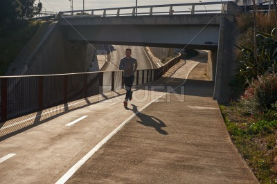 Man running under a bridge along a road
