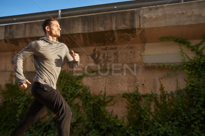 Man sprinting past a brown wall with green plants