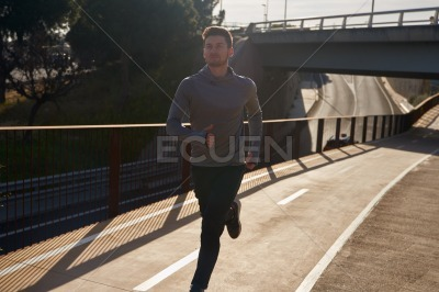 Young man running in athletic gear under a bridge