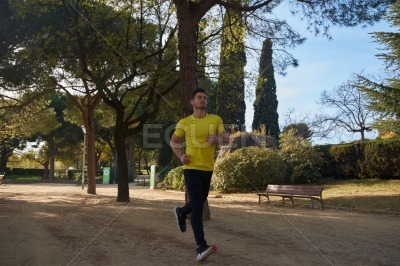 Young man running through a park