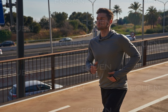 Athletic man running on an overpass