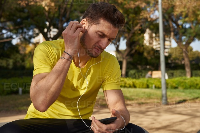 Athletic man seated listening to head phones