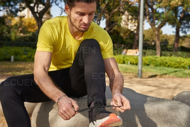 Man dressed in a yellow shirt ties his shoelaces