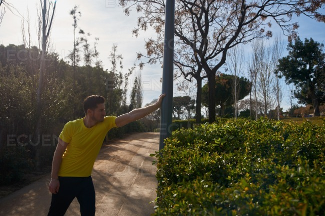 Man holds a pole with one hand as he stretches