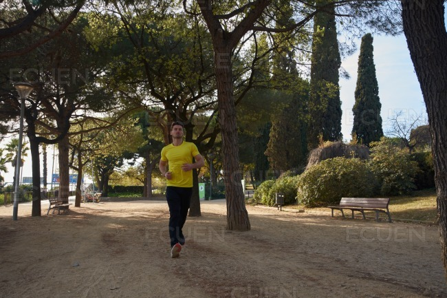 Man in a yellow shirt running through the trees