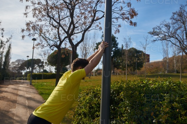 Man leaning against a pole and stretching
