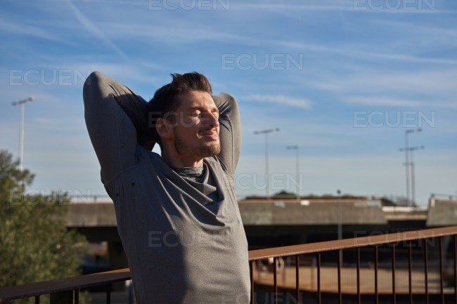 Man looking up with his arms behind his head
