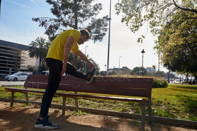 Man raised his leg on a bench as he stretches