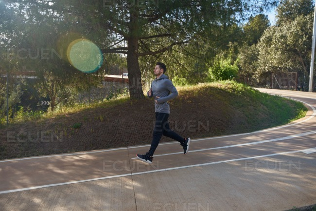 Man running past a hill on a well marked road