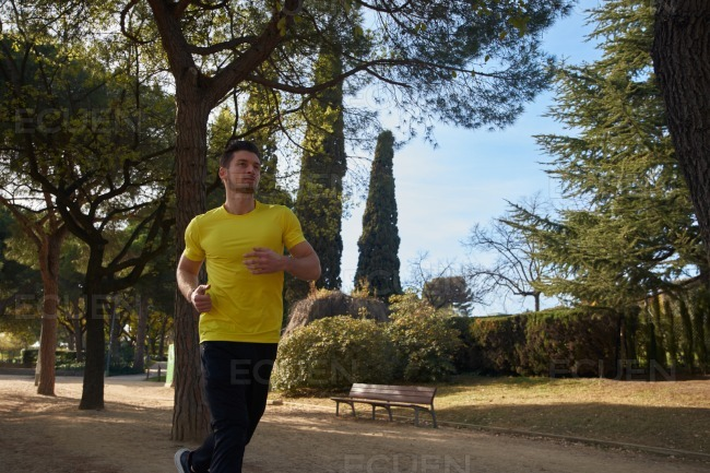 Well muscled young man jogging in a park