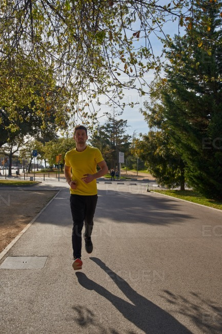 Young man running on a road in a park