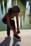 Young slim black woman ties her shoelace