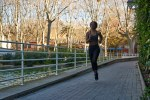 Young woman running along a paved path