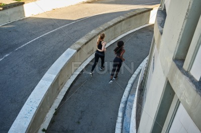 Rear view of two women running a circuit