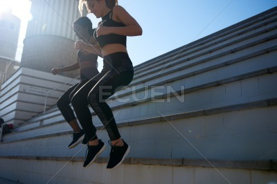 Two women jumping down a step