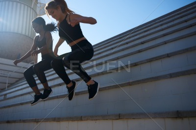 Two women jumping down a step as they exercise