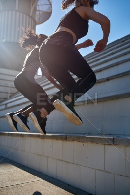 Two women jumping up a series of steps