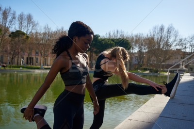 Two women lifting their legs as they exercise