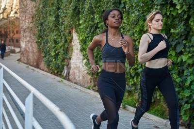 Two women running along a paved path