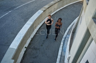 Two women running up a circular path