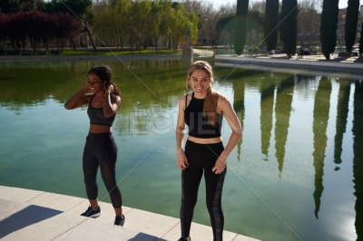 Two women smiling as they exercise outdoors