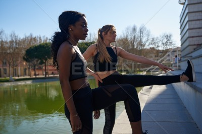 Two women stretching their leg muscles