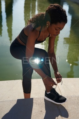 Young ethnic woman ties her shoelace