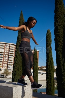 Young woman balancing on a stone pillar