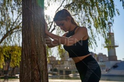 Young woman leans forward facing a tree