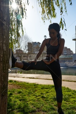 Young woman stretches her leg muscles