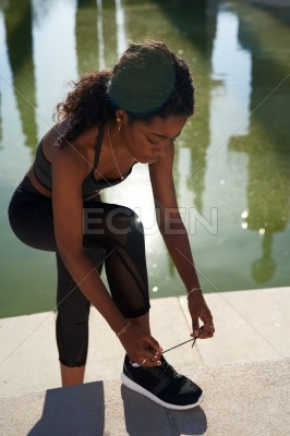 Young woman tying her shoelace of her track shoe