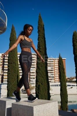 Young woman walking on a stone pillar