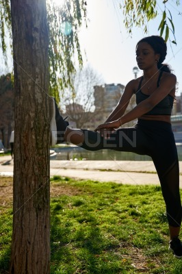Young women stretches her legs against a tree