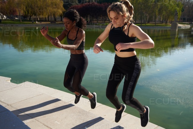 Two women jumping on the spot stock photo