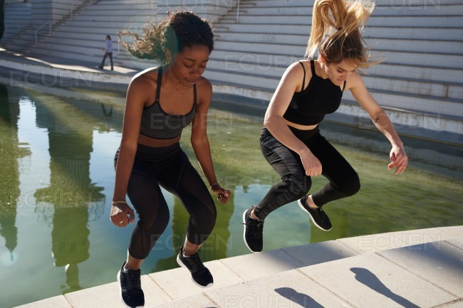 Two women jumping up a step in unison stock photo