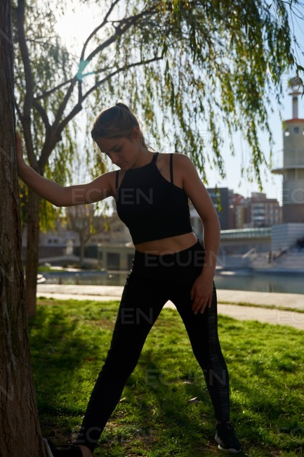 Young woman leans to the side holding onto a tree stock photo