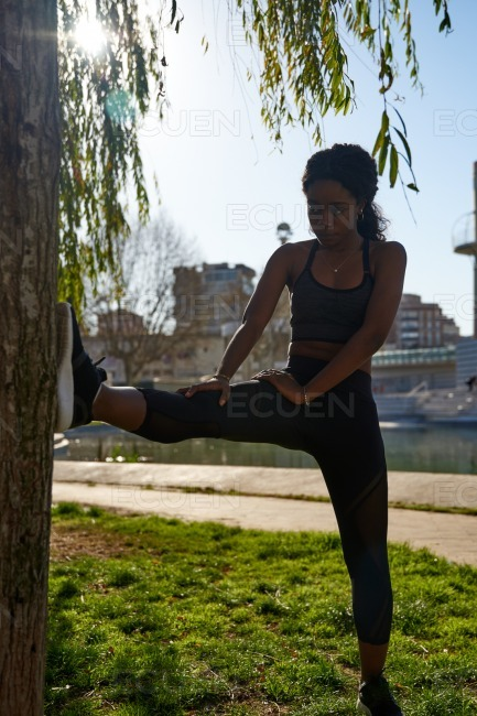 Young woman stretches her leg muscles stock photo