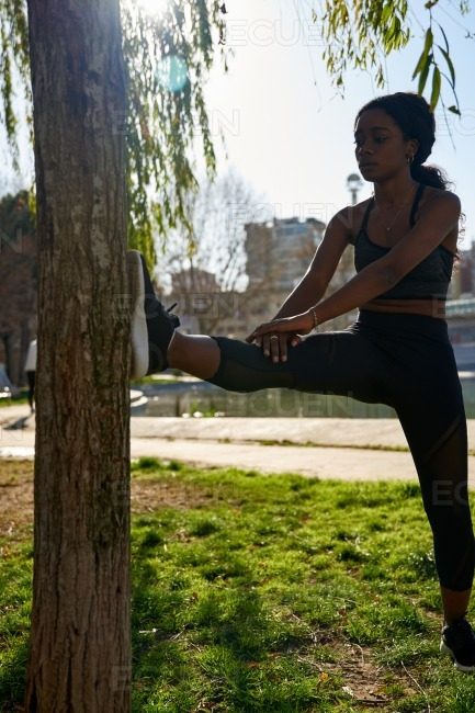 Young women stretches her legs against a tree stock photo