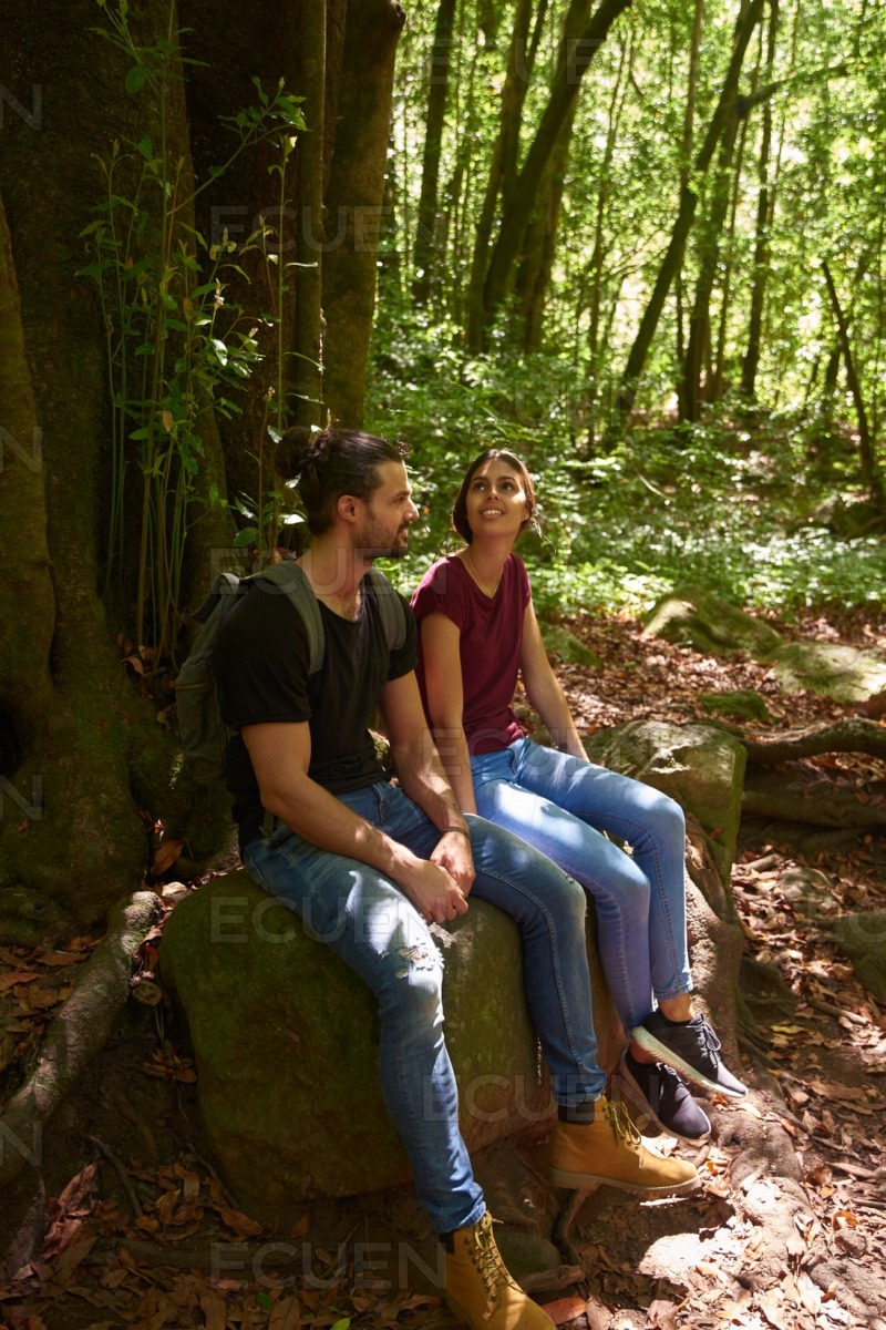 Young couple sitting on a large rock stock photo