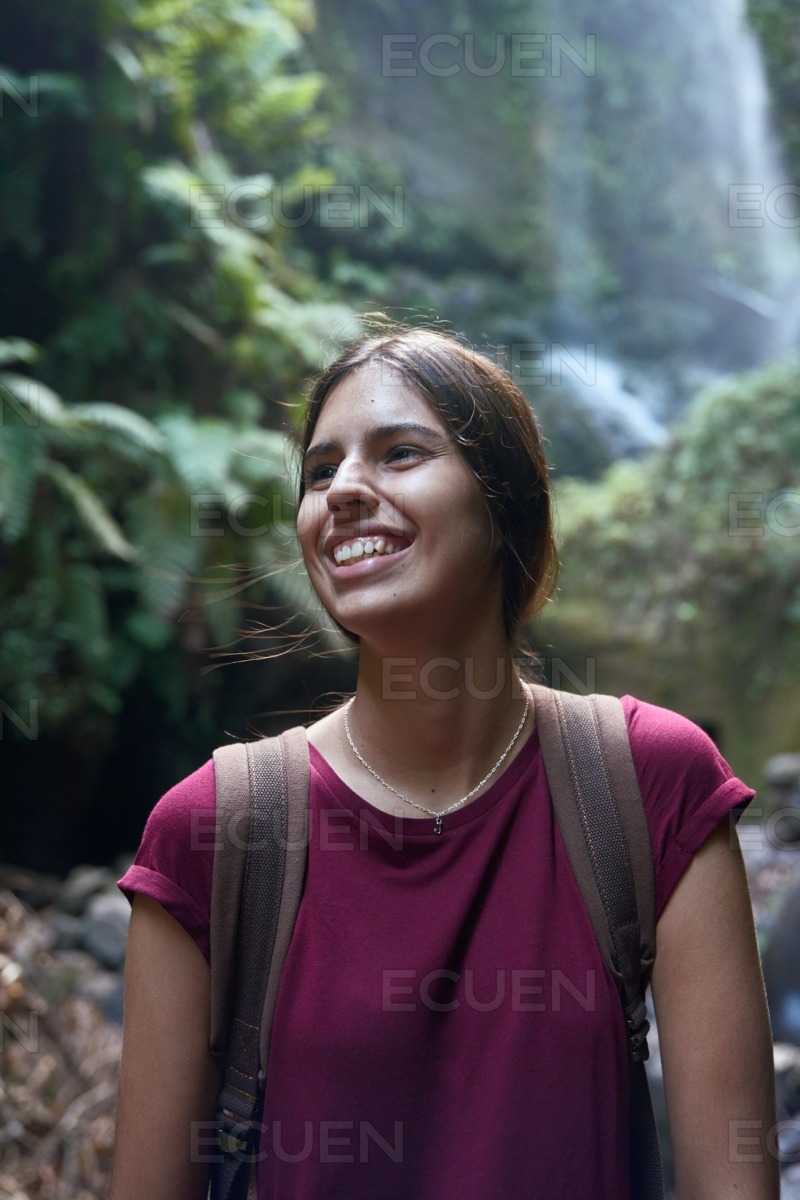 Young woman laughing in front of a waterfall stock photo