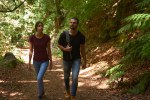 Young couple walk through a lush green forest