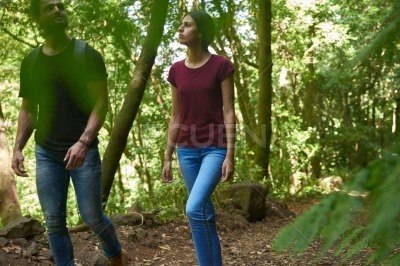 Man and woman strolling among the trees