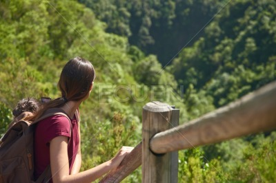 Woman looking at a valley behind her